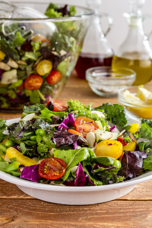 salad greens: Fresh organic super food salad in white bowl with large bowl, olive oil and red wine vinegar in background