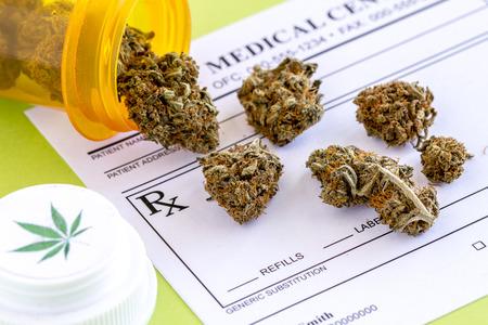 Medical marijuana buds spilling out of prescription bottle with branded lid onto blank medical prescription pad on green background Archivio Fotografico