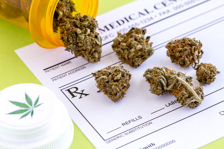 Medical marijuana buds spilling out of prescription bottle with branded lid onto blank medical prescription pad on green background Stock Photo