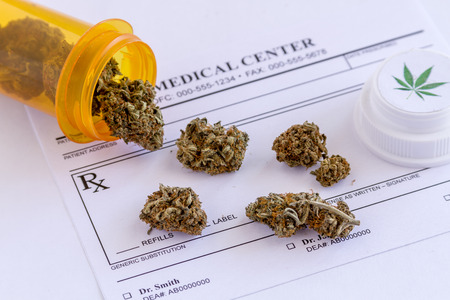 Medical marijuana buds spilling out of prescription bottle with branded lid onto blank medical prescription pad