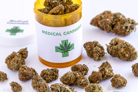 Medical marijuana buds sitting on white table top next to medical cannabis prescription bottle with lid