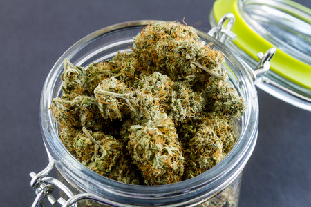 a bud: Close up of medical marijuana buds in glass container on black background Stock Photo