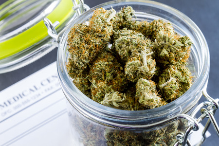 Close up of medical marijuana buds in glass container on black background Foto de archivo