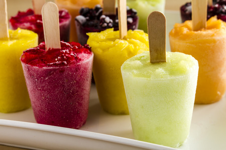 Assorted flavors of homemade fresh pureed frozen fruit popsicles on white plate