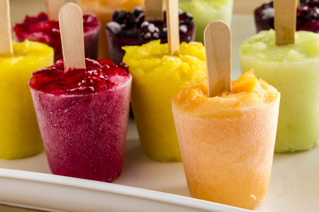 frozen fruit: Assorted flavors of homemade fresh pureed frozen fruit popsicles on white plate