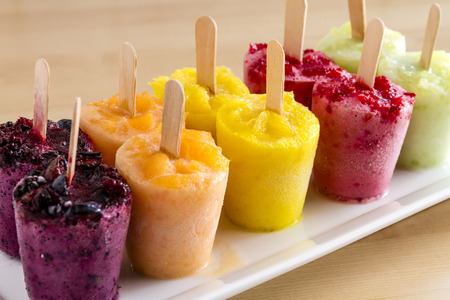 Assorted flavors of homemade fresh pureed frozen fruit popsicles sitting on white plate in a row