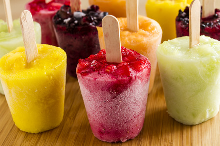 frozen fruit: Assorted flavors of homemade fresh pureed frozen fruit popsicles sitting on wooden cutting board