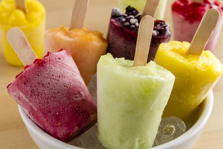 paletas de hielo: Cierre de sabores surtidos de caseros pur� congelado paletas de fruta fresca en un taz�n blanco con hielo