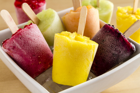 fruta congelada: Close up of assorted flavors of homemade fresh pureed frozen fruit popsicles in white bowl with ice