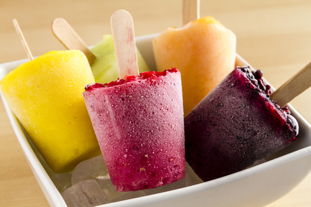 frozen fruit: Close up of assorted flavors of homemade fresh pureed frozen fruit popsicles in white bowl with ice