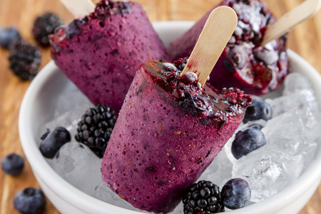 Homemade fresh pureed frozen blueberry and blackberry popsicles in white bowl with ice sitting on wooden table with fresh berries