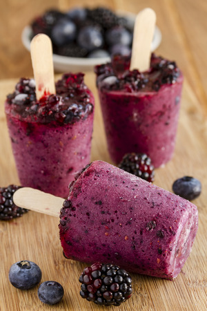 paletas de hielo: Homemade fresh pureed frozen blueberry and blackberry popsicles sitting on wooden cutting board with fresh berries Foto de archivo