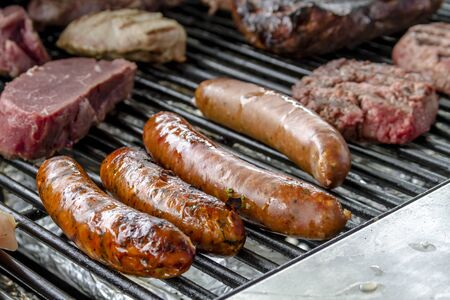 eating dinner: Hamburgers, bratwurst, sausages, tri-tip beef, filet mignon steaks and chicken cooking on grill at summer picnic