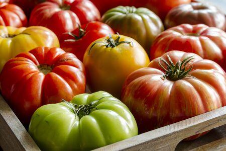 農民市場からの新鮮な自然に育ったエアルーム トマトでいっぱいの木製ボックス