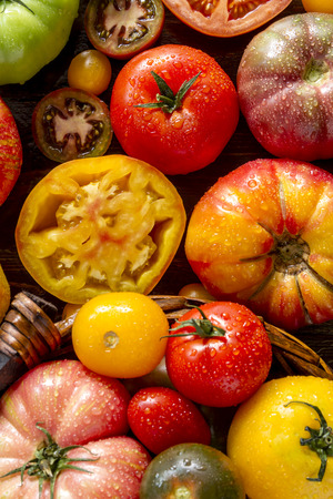 lycopene: Colorful assortment of fresh organic whole and cut heirloom tomatoes sitting on wooden table