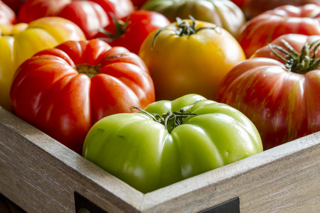 lycopene: Wooden box filled with fresh vine ripened heirloom tomatoes from farmers market Stock Photo