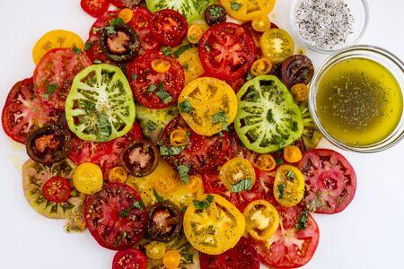 lycopene: Slices of vine ripe heirloom tomato varieties with fresh basil, salt, pepper, olive oil and fresh herbs on white background