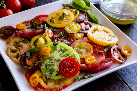 Large square white plate with slices of vine ripe heirloom tomato varieties with fresh basil, salt, pepper, olive oil and fresh herbs