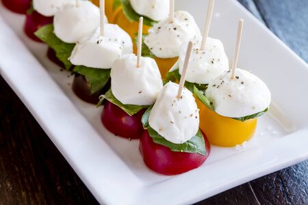 lycopene: Close up of yellow and red cherry tomatoes with fresh basil and mozzarella cheese appetizers sprinkled with salt and pepper sitting on white plate