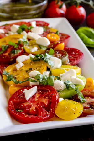 lycopene: Slices of vine ripe heirloom tomato varieties with fresh basil, salt, pepper, olive oil and fresh herbs sitting on square white plate