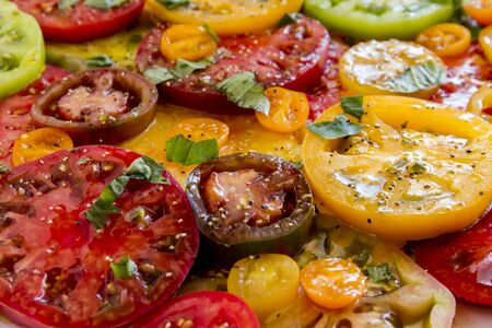 lycopene: Close up of slices of vine ripe heirloom tomato varieties with fresh basil, salt, pepper, olive oil and fresh herbs