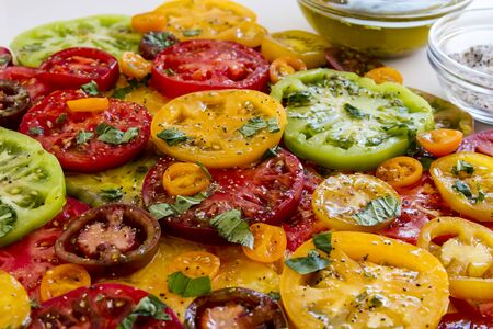 lycopene: Close up of slices of vine ripe heirloom tomato varieties with fresh basil, salt, pepper, olive oil and fresh herbs on white background Stock Photo