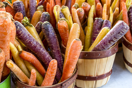 colorful buckets filled with fresh organic rainbow carrots Stock Photo