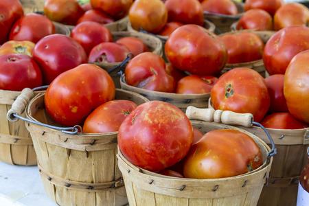 bushel: Fresh organic red tomatoes in brown bushel baskets Stock Photo