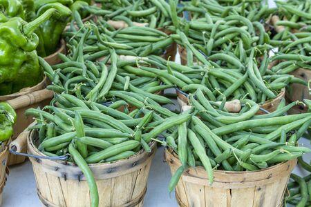 bushel: Fresh organic green string beans in brown bushel baskets