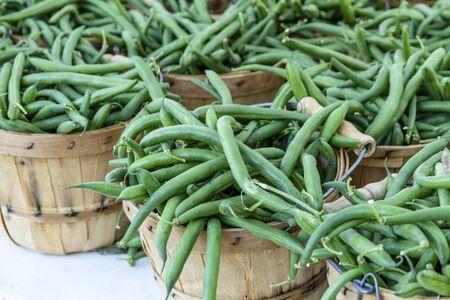 bushel: Fresh organic green string beans in brown bushel baskets sitting on table at local farmers market