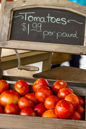 roadside stand: Fresh picked organic red tomatoes with chalkboard sign for sale  at local roadside produce stand Stock Photo
