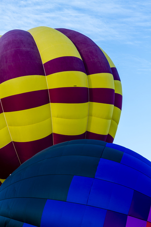 weightless: Brightly colored hot air balloon against blue morning sky getting inflated before take off Stock Photo