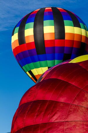 buoyant: Brightly colored hot air balloons against blue morning sky on the ground and just after take off Stock Photo