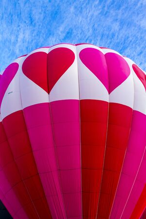 corazones azules: Top of brightly colored red and pink hot air balloon with hearts against blue morning sky as it gets inflated for flight Foto de archivo