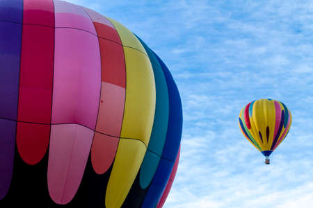 buoyant: Brightly colored hot air balloon against blue morning sky on the ground before take off and balloon in the air