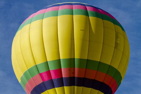 weightless: Top of brightly colored hot air balloon against blue morning sky just after take off Stock Photo