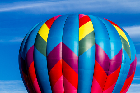 buoyant: Brightly colored hot air balloon against blue morning sky on the ground before take off