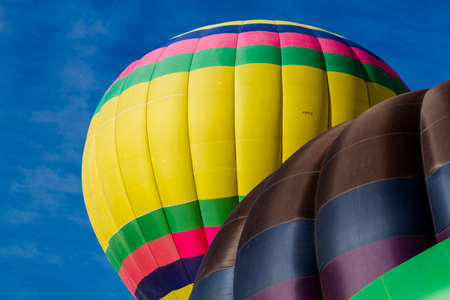 buoyant: Top of brightly colored hot air balloons against blue morning sky just after take off