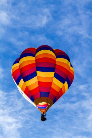 on off: Brightly colored hot air balloon against blue morning sky just after take off
