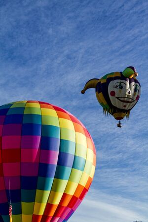 buoyant: Brightly colored hot air balloon against blue morning sky on the ground before take off and joker head shaped balloon in the air Stock Photo