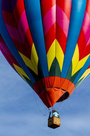 buoyant: Brightly colored hot air balloon against blue morning sky just after take off