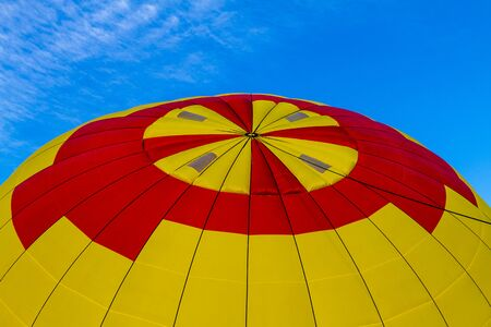 weightless: Top of brightly colored yellow and red hot air balloon against blue morning sky