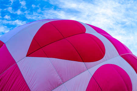 weightless: Top of brightly colored red and pink hot air balloon with hearts against blue morning sky as it gets inflated for flight Stock Photo