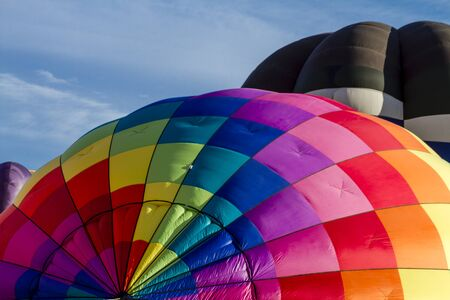 weightless: Brightly colored hot air balloon against blue morning sky on the ground before take off