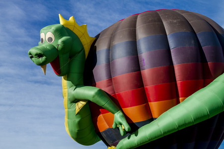 buoyant: Hot air balloon with dragon shaped surrounding balloon on ground before take off