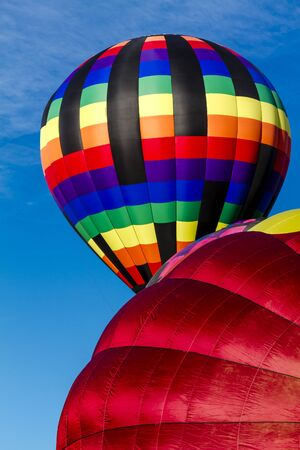 weightless: Brightly colored hot air balloons against blue morning sky on the ground and just after take off Stock Photo