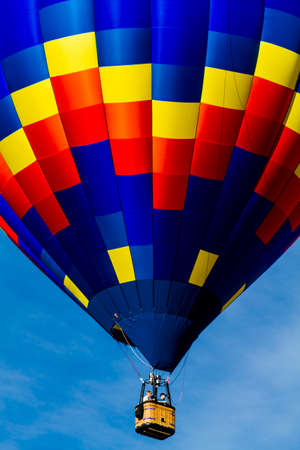 weightless: Brightly colored hot air balloon against blue morning sky just after take off