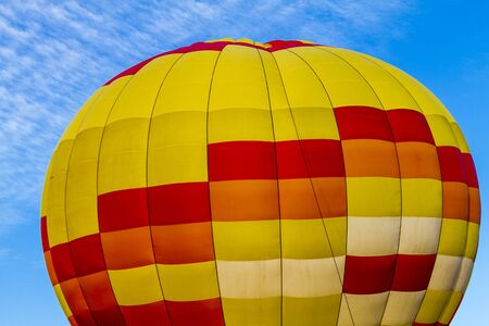 weightless: Brightly colored yellow and red hot air balloon against blue morning sky tethered to the ground before take off