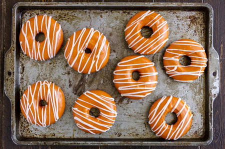 Baking pan filled with homemade baked pumpkin donuts with orange pumpkin glaze and apple cider drizzle Stock Photo