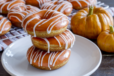 Stack of homemade baked pumpkin donuts with orange pumpkin glaze sitting on white plate with small pumpkins in background